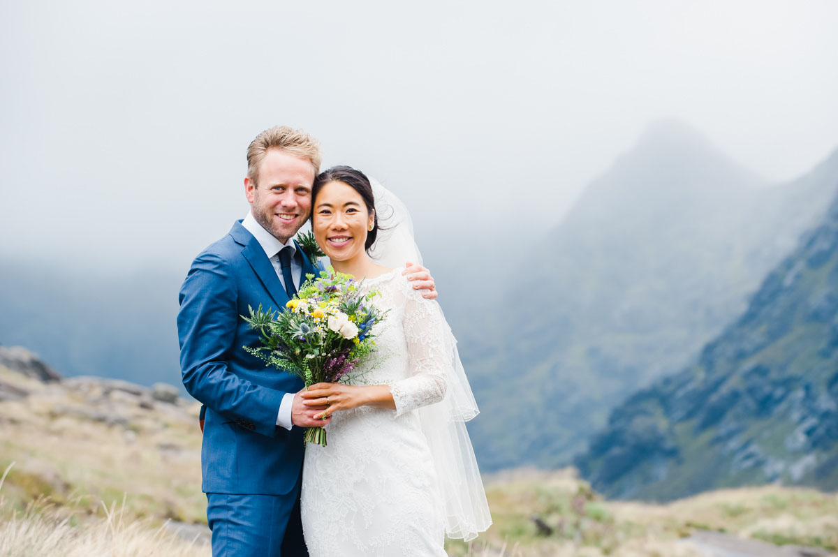 Wedding photograph of a groom in a blue suit with his arm around his bride, both holding a bouquet, with a mountain beyond