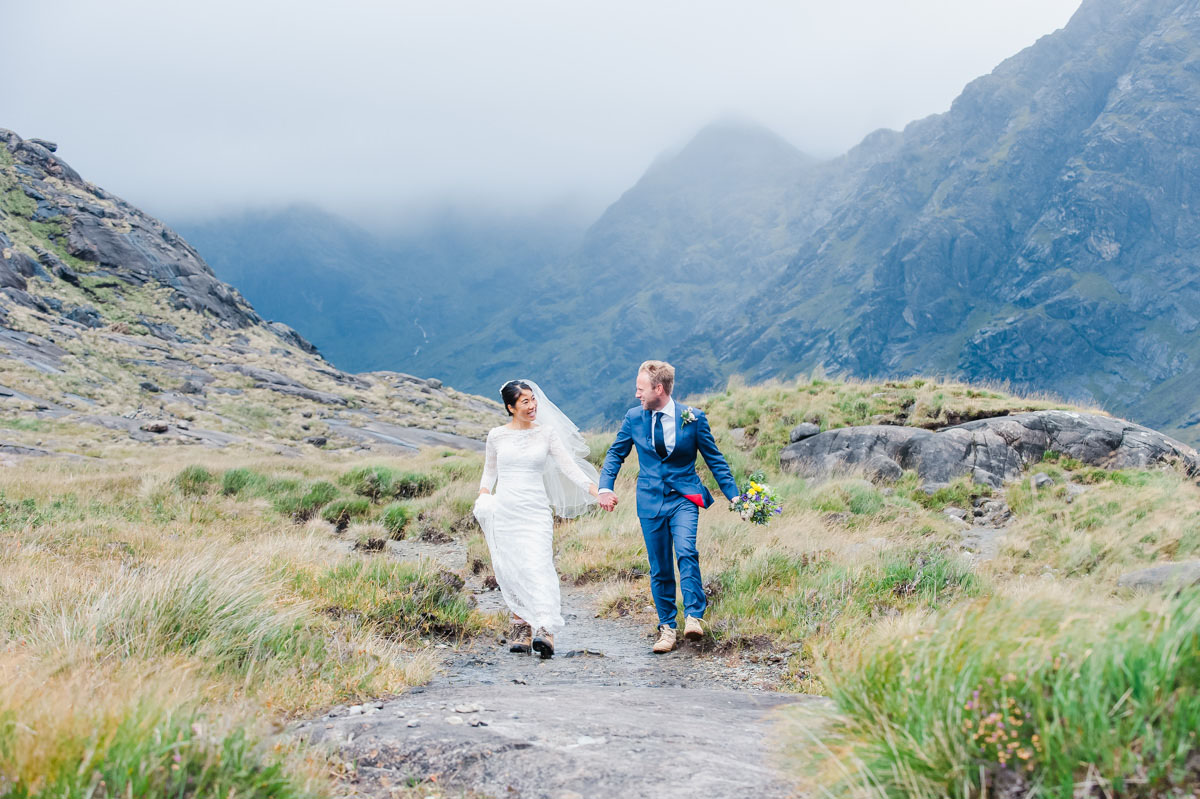 Wedding photograph of a bride and groom holding hands and smiling, walking on a rock next to grass in front of mountains