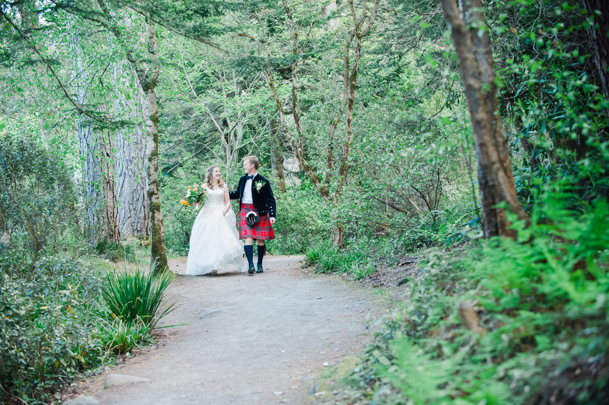 Wedding photograph of a bride and groom smiling at each other while walking on a path through a woodland