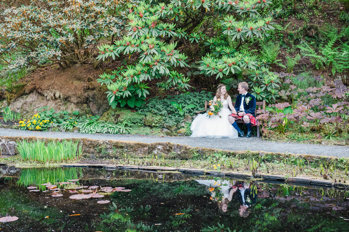Wedding photo of a bride and groom sitting on a bench in front of rhododendrons, with their reflection in a pond