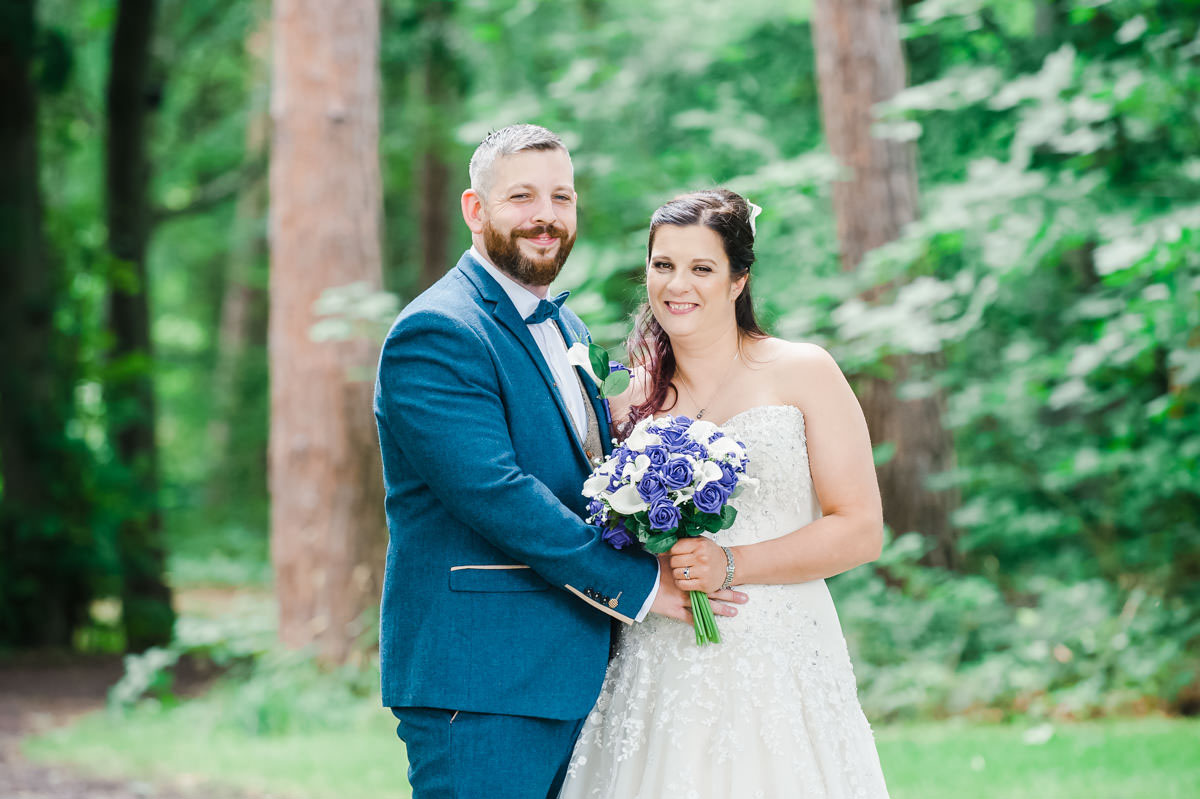 Wedding photo of a bride wearing a white dress and holding flowers, beside a groom in a blue suit, both smiling, in woodland