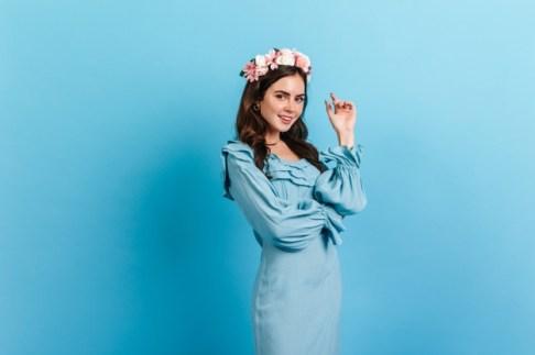 mujer-joven-maquillaje-nude-flores-pelo-senora-vestido-azul-cielo-posando-pared-aislada_197531-14292