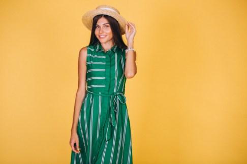 mujer-vestido-verde-sombrero-sobre-fondo-amarillo_1303-10114