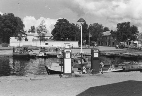 Sorvakon rannasta vuonna 1956 otetun kuvan keskeisinä elementteinä veneiden tankkauspaikan polttoainesäiliöt. Kaupunginlahden toisella puolella Kalaranta ja Rantakadun kioskeja eli paikallismurteella putkuja, joista yksi on avoimesta luukusta päätellen vielä auki. Koulukadun ja Rantakadun kulmassa olevassa rakennuksessa toimi pitkään sekatavarakauppa, joka totteli paikallisväestön suussa nimeä Kolmen herram puar. Talo purettiin 1970-luvun alussa Osuuspankin nykyisen toimitalon tieltä. Kuvaaja Olavi Ruusuvuori.