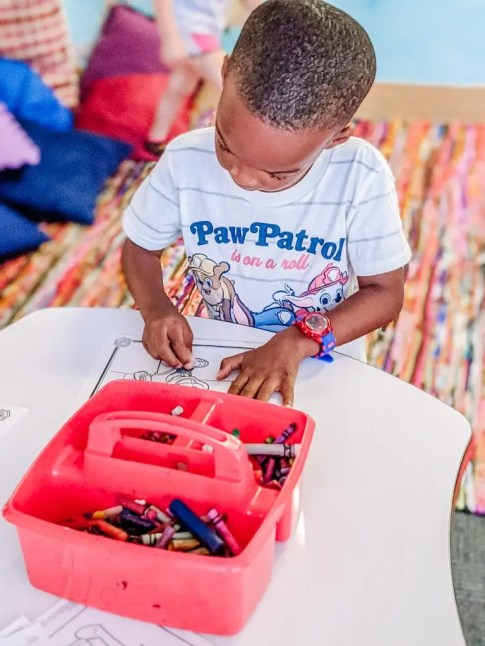 Black boy coloring at Glazer Children's Museum
