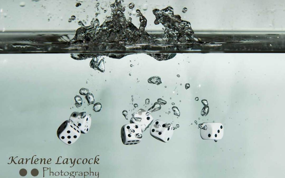 White Dice falling into water on grey series 4
