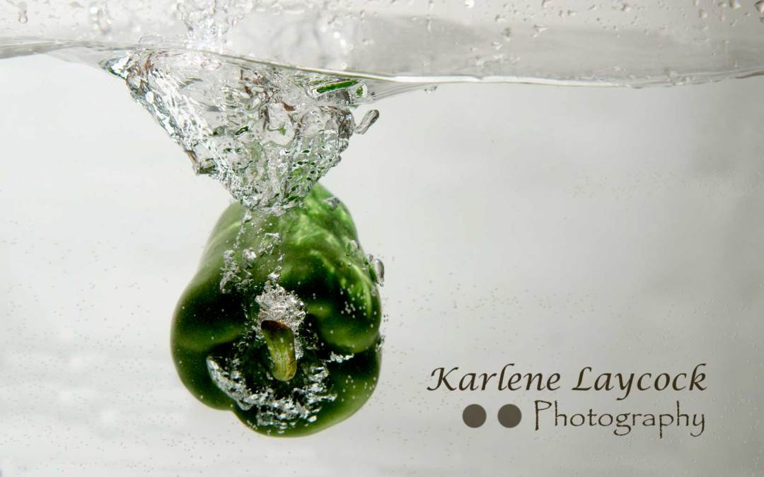 High Speed Photography – Image of a Green Pepper submerged in Water Creating a Wave