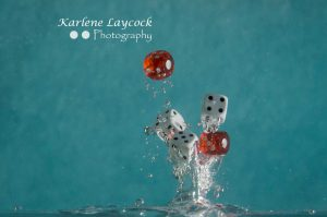 Red Dice falling into water on blue 3