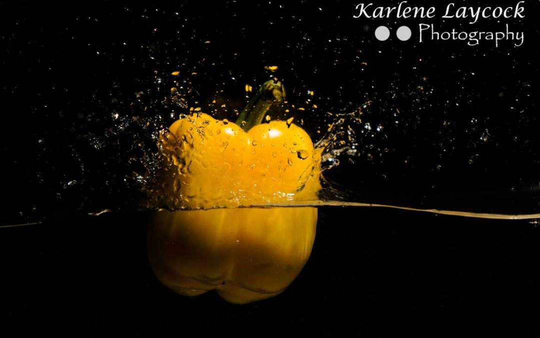 Yellow Pepper dropping into water on black background 1