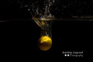 Lemon dropping into water on black background 1