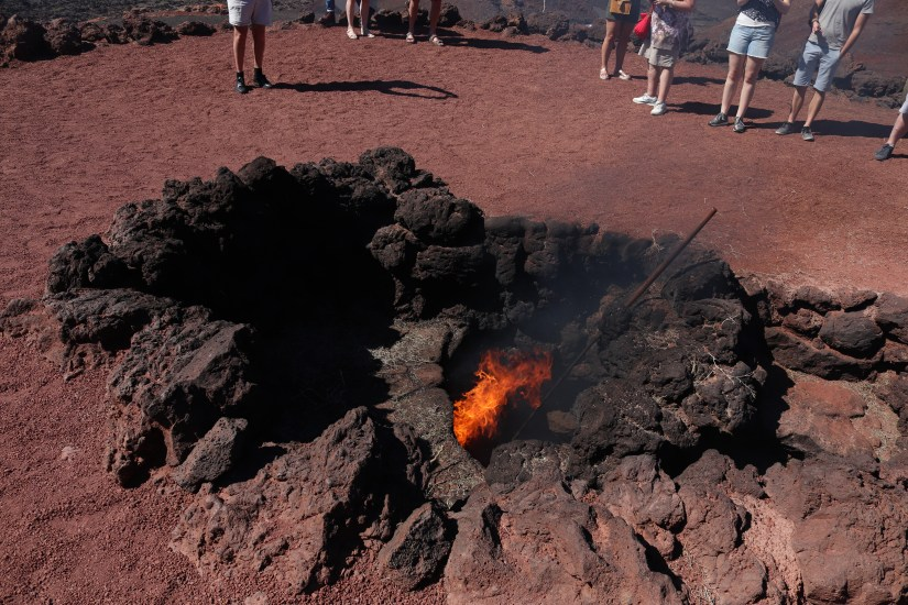 Creating fire using volcanic heat in Timanfaya National Park