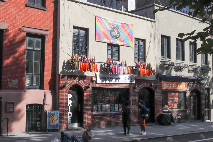 The front of the Stonewall Inn with pride flags flying outside.