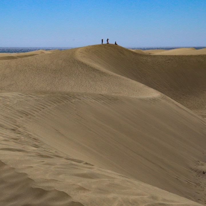 Crescent shaped sand dunes curve into the distance. The silhouettes of three people can be seen stood at the highest point of the sand dunes.