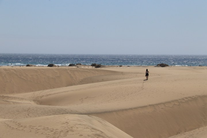 a view towards the sea from the Maspalomas Sand dunes. A person is wandering towards the sea leaving foot prints in the sand behind her.