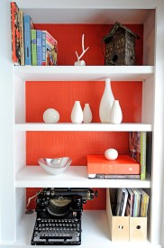 Fully adjustable shelves sit on each side. Striking wallpaper and paint selections bring life to the bright white unit.