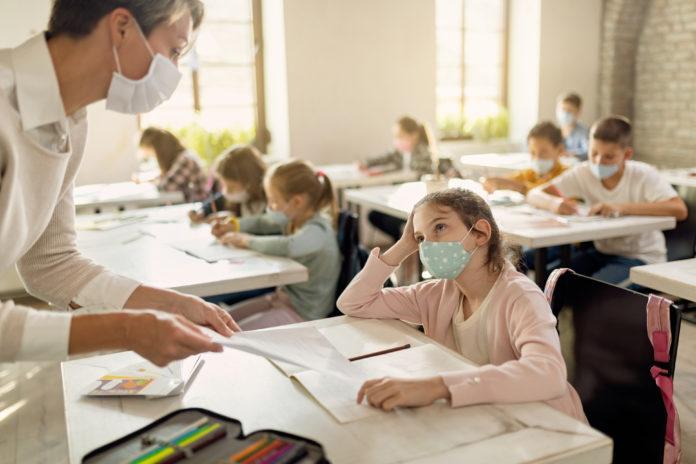 schüler in einem klassenzimmer während der corona-zeit