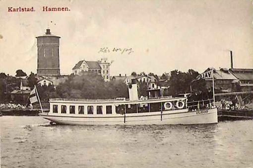 Turbåten Vålösund i hamnbassängen med träslotten på Herrhagsberget i bakgrunden