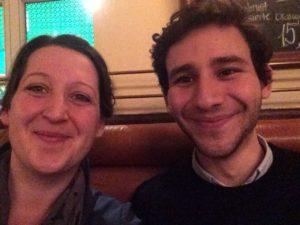 Hier ist ein Bild von zwei Menschen in einem schlecht beleuchteten Lokal zu sehen, die fröhlich in die Kamera lächeln