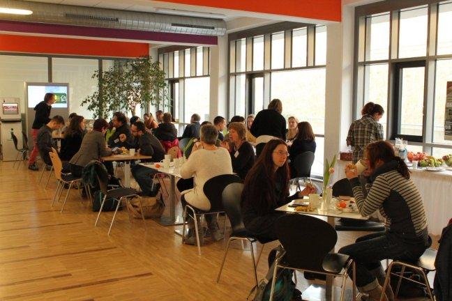 Hier ist ein Bild der Teilnehmenden am BleibGesundCamp in Esslingen zu sehen. Verschiedene Gruppen von Menschen sitzen an Tischen.