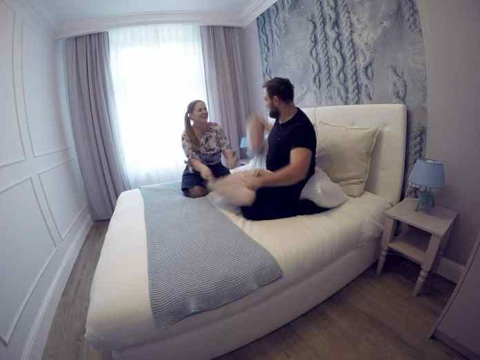 pillow fight couple white sheet bed smile laugh