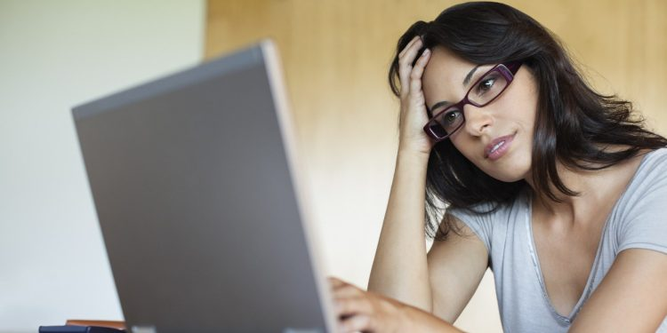 Frustrated woman using laptop