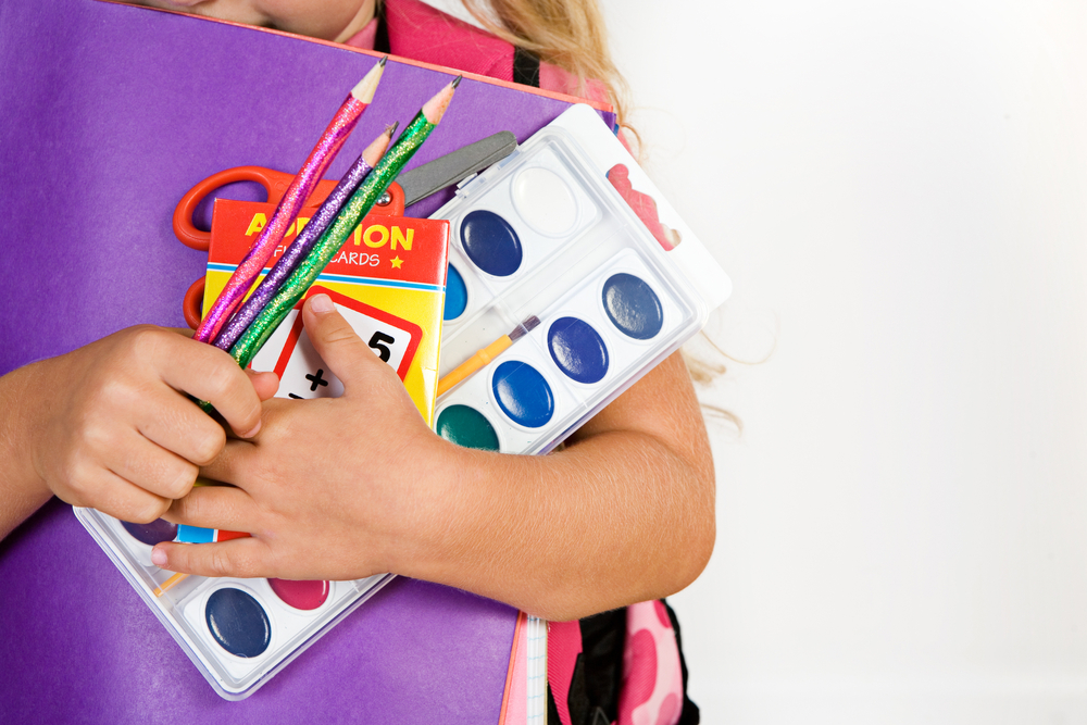 Child hugs school supplies to her chest