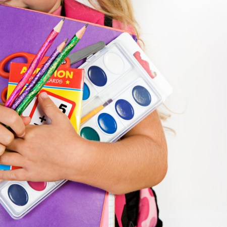 Child hugs school supplies to her chest