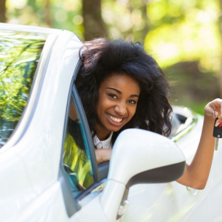 Jubilant black teen holding car keys while sitting in white convertible