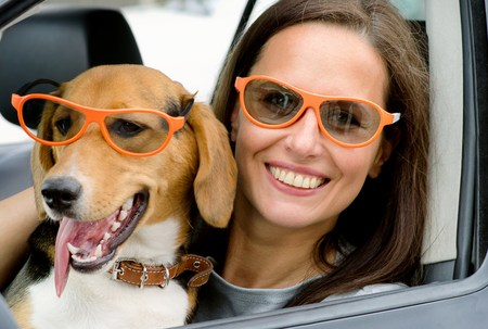 Woman driver holding dog, both wearing orange framed sunglasses