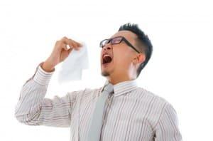 Asian man sneezes
