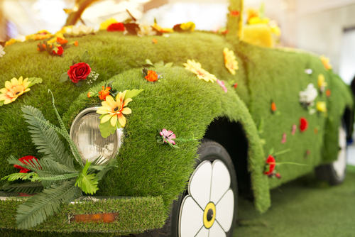 car covered with grass and flowers