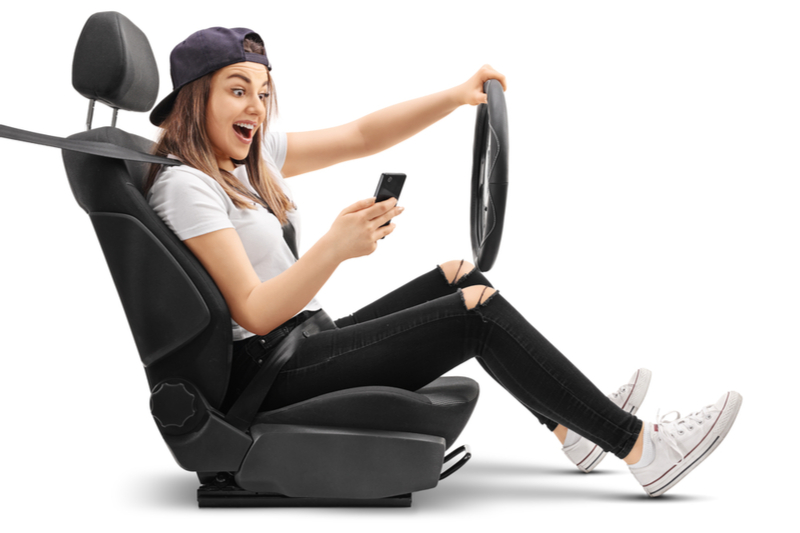 Teenage girl simulates driving while looking at her phone