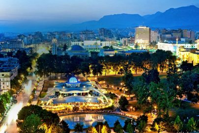 D03FNN Dusk view of Tirana, the capital of Albania. In the foreground is Rinia Park.