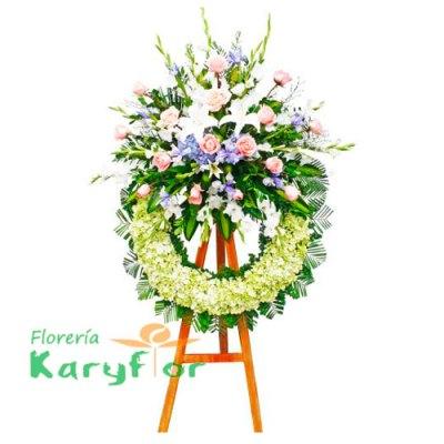 Corona floral con rosas importadas, lilium, gladiolos, hortencia,variedad de flores y fino follaje en trípode. Incluye tarjeta impresa de condolencia.