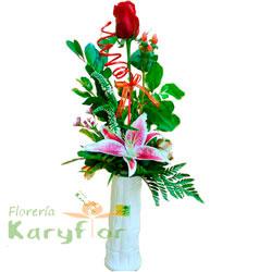 Arreglo floral elaborado en florero de cerámica blanca, contiene 1 rosa importada, lilium perfumado, verónica, fino follaje. Incluye tarjeta de dedicatoria. Pueden adicionar Chocolates y más, ingresando a la opción REGALOS en la parte superior de la Pág. web.