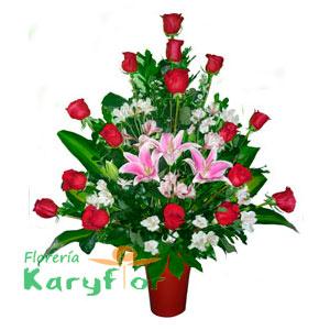 Delicado arreglo floral compuesto por rosas importadas, claveles, lilium, fino follaje en florero de cerámica. Incluye tarjeta dedicatoria