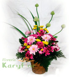 Arreglo floral primaveral elaborado en canastilla de cerámica.