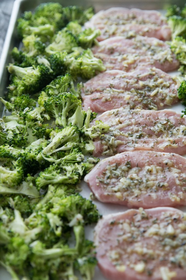 pork chops on a baking sheet with broccoli ready to go in the oven