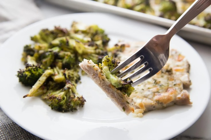oven baked pork chops with broccoli plated with a bite on the fork