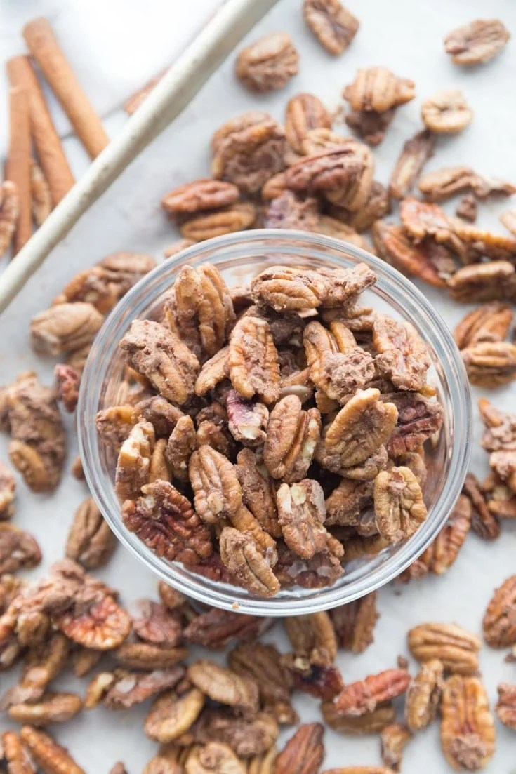 Cinnamon Candied keto pecans on a baking sheet and in a jar