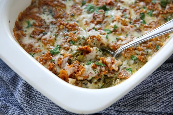low carb green bean casserole out of the oven in a casserole dish with a spoon in it