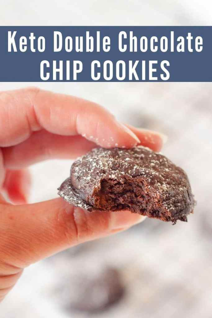 hand holding a keto double chocolate chip cookie with a bite taken out of it
