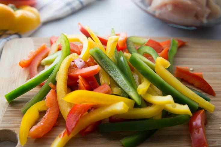 sliced bell peppers in a variety of colors on a cutting board for Keto chicken fajitas