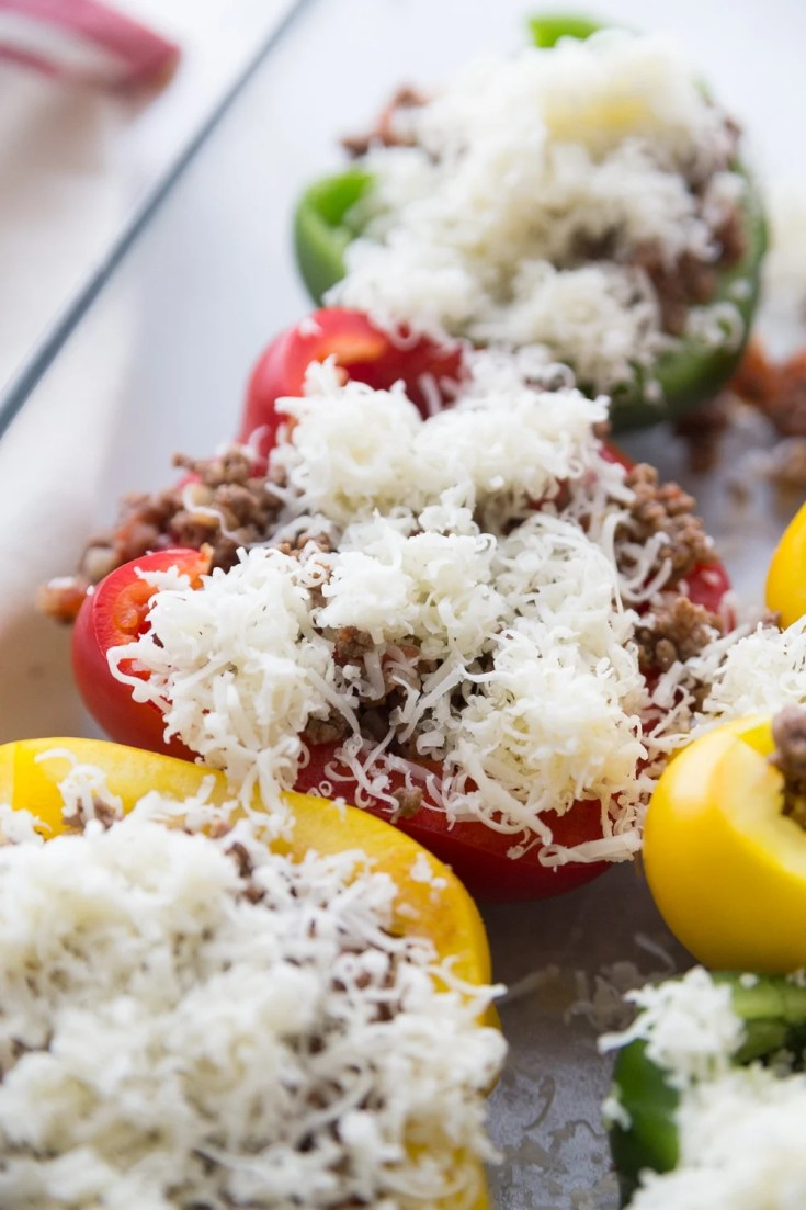 Cheese being sprinkled on top of the bell peppers of the keto stuffed peppers recipe