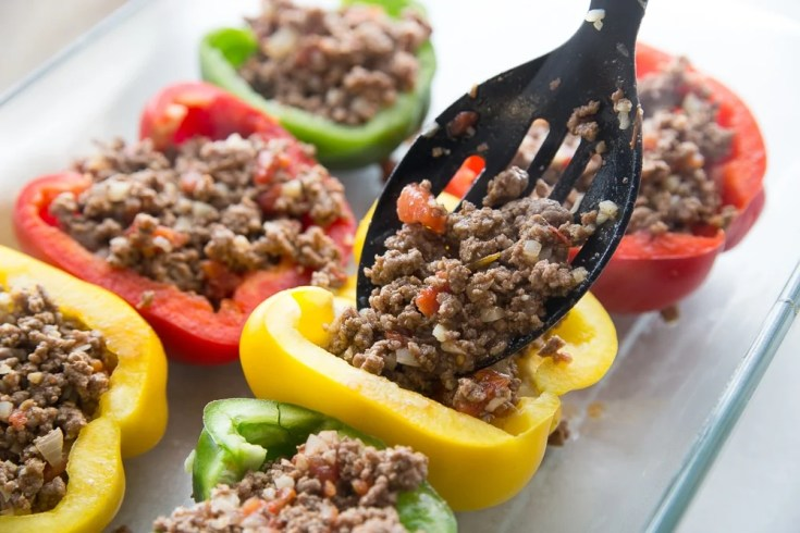 Ground beef mixture being put in bell peppers for low carb stuffed peppers