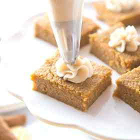 keto pumpkin pie bars with a dollop of cream cheese frosting