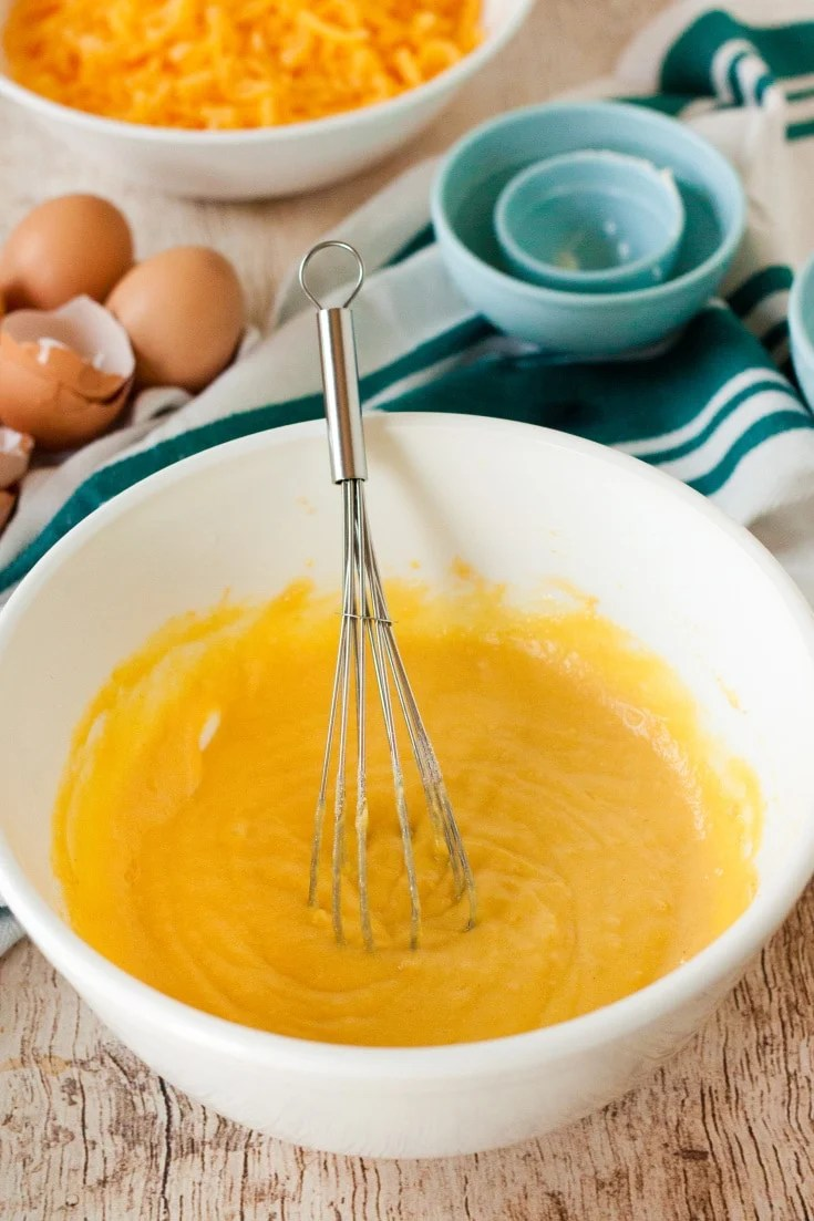 white mixing bowl with melted butter and eggs