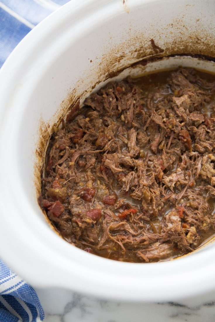 shredded slow cooker pot roast in a slow cooker