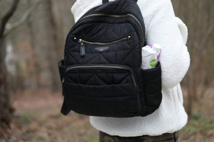 lady from behind with a backpack diaper bag and a ZonePerfect Keto Shake in the pocket on bag