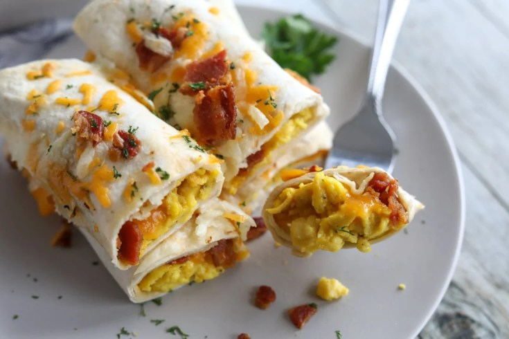 Four burritos stuffed with bacon, cheese and eggs stacked on a plate.